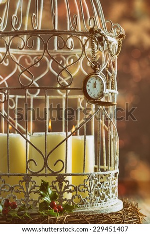 Pocket watch showing midnight on birdcage filled with candles - stock photo