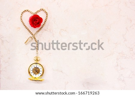 Pocket watch with heart shape chain and red rose on marble. Vertical version at Image ID: 166719260. - stock photo