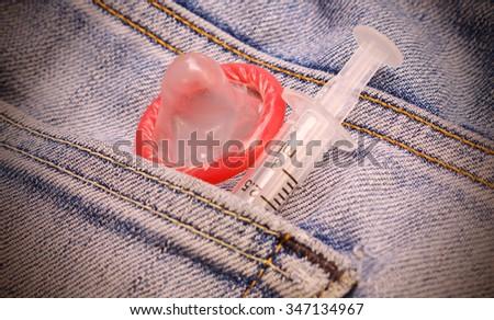Pocket with condom vintage color tone . - stock photo