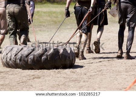 POCONO MANOR, PA - APR 29: A team runs on a trail dragging a large tire as an extra challenge at Tough Mudder on April 29, 2012 in Pocono Manor, Pennsylvania. British Royal troops designed the course. - stock photo