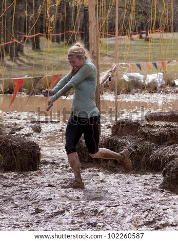 POCONO MANOR, PA - APR 28: A woman runs through an obstacle with electrified wires at Tough Mudder on April 28, 2012 in Pocono Manor, Pennsylvania. The course is designed by British Royal troops. - stock photo