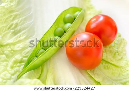 Pod peas and cherry macro. - stock photo