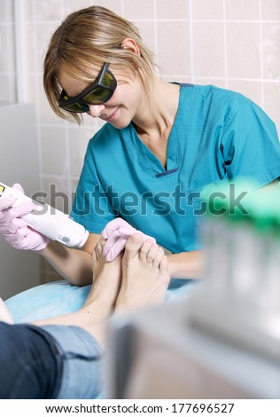 Podiatrist doing a foot laser treatment on a woman to kill fungal infections of the nail, remove unwanted hair and rejuvenate the skin - stock photo