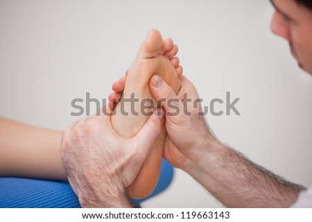Podiatrist practicing reflexology on the foot of woman in a room - stock photo