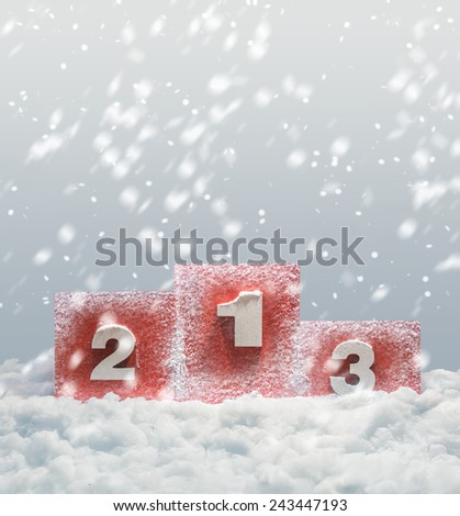 Podium with 1 2 and 3 positions with falling snow - stock photo