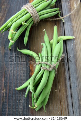pods of green peas on a wooden table - stock photo