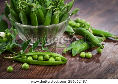 Pods of peas on a wooden table - stock photo