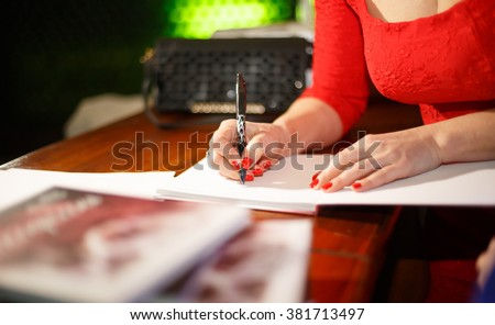 Poetess girl autographs in his new collection of poems. Woman writer gives an autograph book. Autograph for readers and fans - stock photo