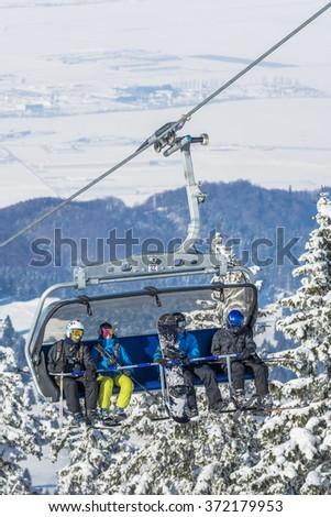 POIANA BRASOV, ROMANIA - JANUARY 24, 2016: Tourists in chairlift in winter season going to the ski slope in resort Poiana Brasov, Romania - stock photo