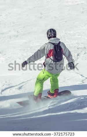 POIANA BRASOV, ROMANIA - JANUARY 24, 2016: Young snowboarder sliding on ski slope during winter season in Poiana Brasov resort, Romania - stock photo