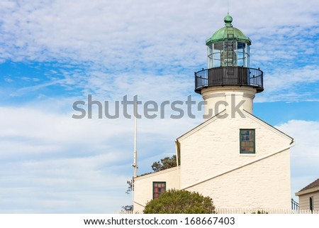 Point Loma lighthouse profile. Side view of white building. Fresnel lens visible in tower. Cloudy blue sky background. Room for text, copyspace. Horizontal photo. - stock photo