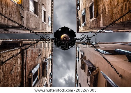point of view of a dark alley with gloomy sky in Venice, Italy - stock photo