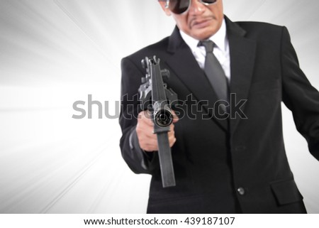 Pointed gun of a man in black suit, crime action movie concept background, with dramatized effect - stock photo