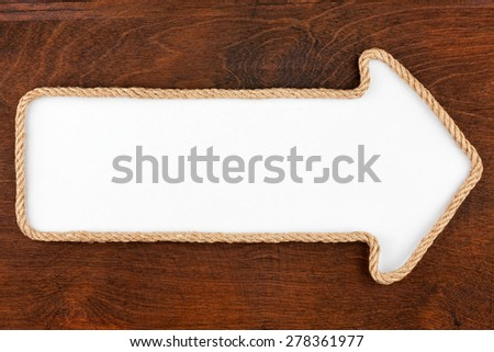 Pointer made of rope with a white background on the wood, with place for your text - stock photo