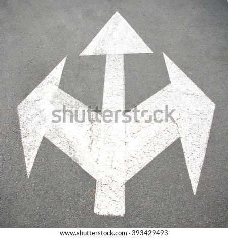 pointer  with an arrow painted on the road - stock photo