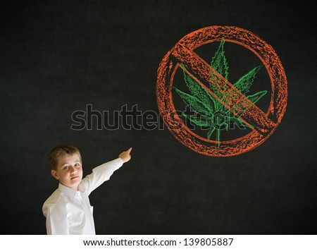 Pointing boy dressed up as business man with no weed marijuana on blackboard background - stock photo