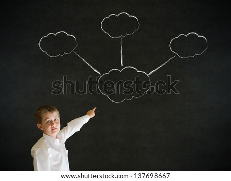 Pointing boy dressed up as business man with strategy thought chalk clouds on blackboard background - stock photo