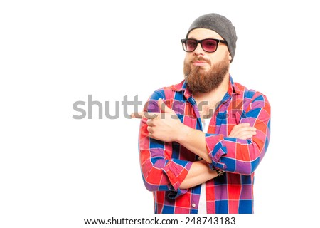 Pointing copy space. Bearded young man in sunglasses looking at camera and pointing away while standing isolated on white background - stock photo