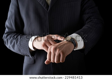 Pointing to the clock face shot of a caucasian man in a business suit, low-key dramatic light composition - stock photo