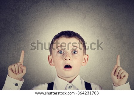 Pointing up surprised  little boy isolated over white background. - stock photo