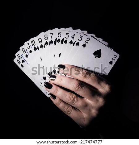 poker cards in hand on dark background - stock photo