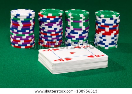 Poker chips and cards closeup on green cloth - stock photo