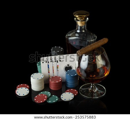 Poker chips and cognac on black cloth - stock photo