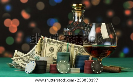 Poker chips and dollar bills with cognac glass - stock photo