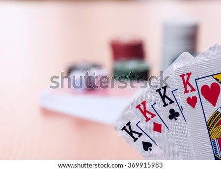 Poker chips and generic playing cards. Courts for poker chips and dice on wooden table - stock photo