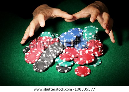 Poker chips and hands above it on green table - stock photo