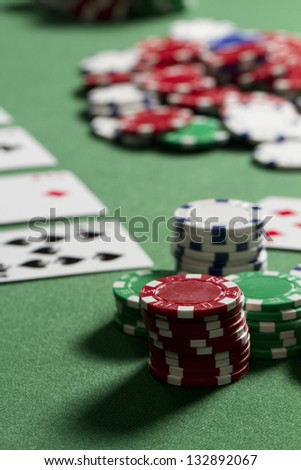Poker Chips Stack a vertical shot of poker chips from a players point of view. chips are out of focus in middle pot. - stock photo
