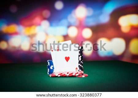 Poker chips with aces cards on table in casino - stock photo