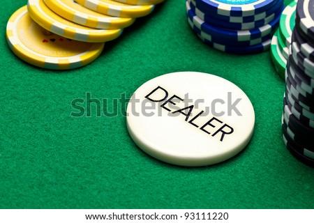 Poker dealer button and chips on green felt - stock photo