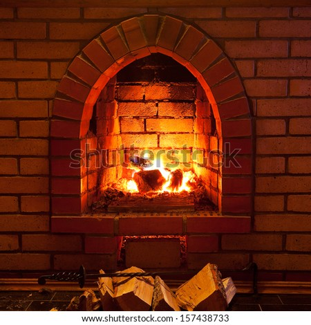 poker, firewood and flames of fire in fireplace in evening time - stock photo
