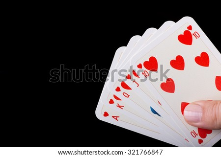 Poker hand of Royal flush of hearts against black background - stock photo
