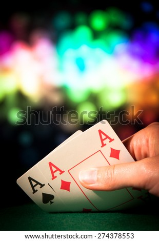 Poker hand with two aces in casino colorful background - stock photo