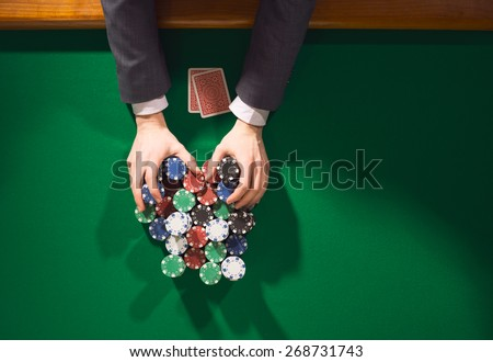 Poker player betting all in and holding a lot of chips stacks, hands close up, top view - stock photo