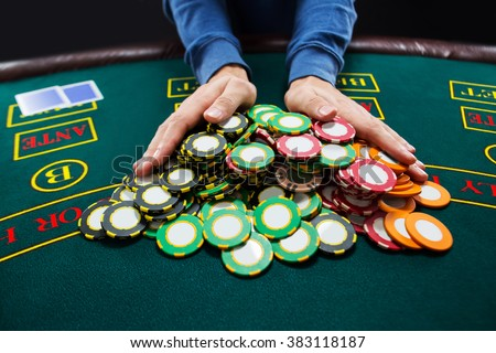 Poker player going all-in pushing his chips forward - stock photo