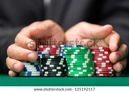 "Poker player going ""all in"" pushing his chips forward. Addiction to the gambling - stock photo"