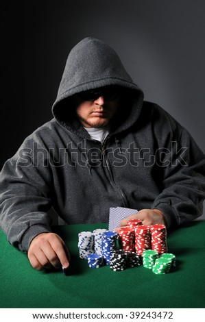 Poker player holding chip staring through sunglasses - stock photo