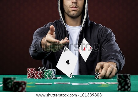 Poker player, on a red background, throwing two ace cards. - stock photo