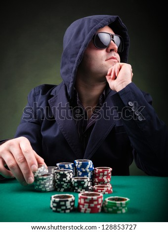 Poker player on black background - stock photo