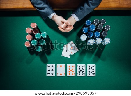Poker player's hands with cards and stacks of chips all around on green table, top view - stock photo