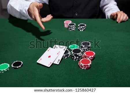 Poker player throwing down a pair of aces as he declares his hand and folds during a game of poker at a casino gaming table - stock photo