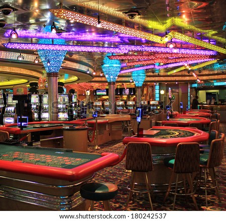 Poker table and gaming slot machines in American gambling casino. - stock photo