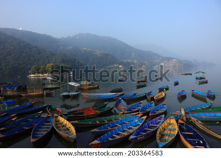 POKHARA, NEPAL - FEB 06: Tourist boats float on the Fewa lake in the morning on February 06, 2014 in Pokhara, Nepal. Pokhara is a popular tourist destination known for trekking and boating. - stock photo