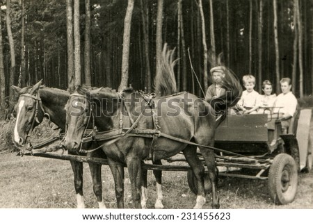 POLAND, CIRCA SIXTIES: Vintage photo of parents with little son traveling by horse-drawn carriage - stock photo