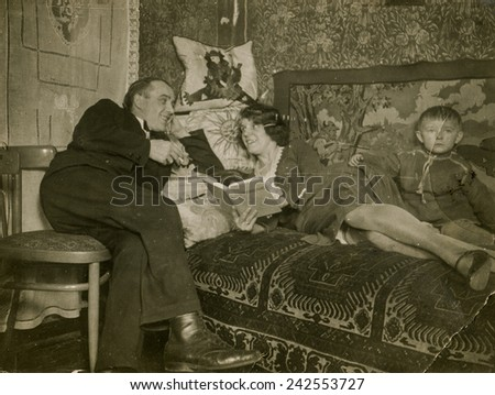 POLAND, CIRCA THIRTIES: Vintage photo of a woman reading a book on bed, with her husband and little son - stock photo