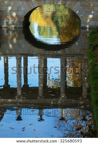 Poland.Warsaw.Lazienki Royal park in autumn.October.View of the bridge and reflection in the water.Vertical view. - stock photo