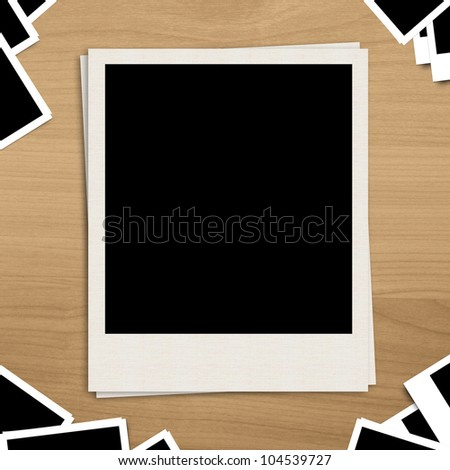 Polaroid blank photo frame on brown wooden background - stock photo
